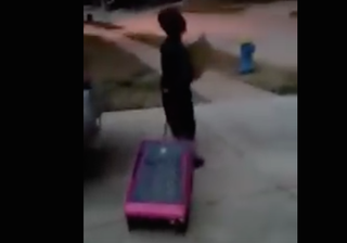 A young boy is seen in video walking down the sidewalk pulling his suitcase after his mother reportedly kicked him out for voting for Donald Trump in a mock school election. YouTube screenshot