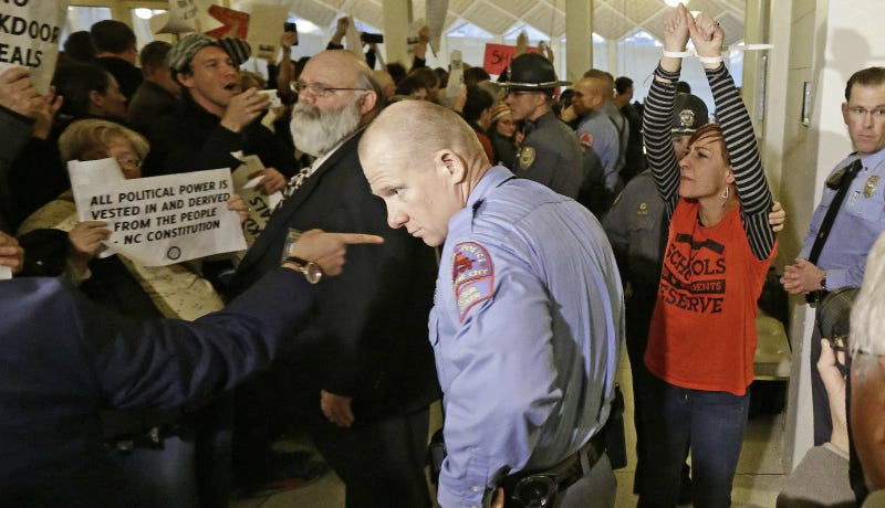 A protestor, right, is handcuffed and removed from the House gallery as demonstrators interrupted a special session at the North Carolina Legislature in Raleigh, N.C., Thursday, Dec. 15, 2016. Photo via AP