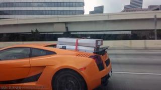 Lamborghini Gallardo carrying two TV's on top of the engine bay....