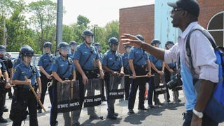 A resident of Ferguson, Mo., speaks to Missouri Highway Patrol officers in riot gear outside Ferguson Police Department Headquarters during a protest of the shooting death of 18-year-old Michael Brown by a Ferguson police officer Aug. 11, 2014.Michael B. Thomas/Getty Images