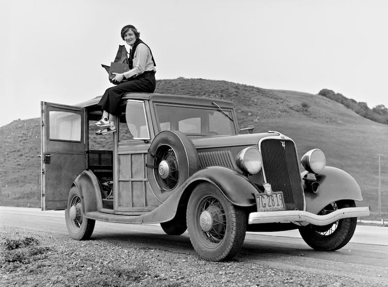 Lange sits atop a Ford Model 40 in California in 1936. She is holding a Graflex 4×5 Series D camera. (US Library of Congress)