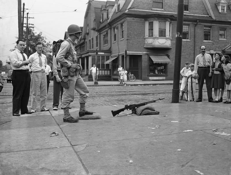 A soldier stands guard with an automatic rifle at the carbarn at 49th Street and Woodland Avenue in Philadelphia on Aug. 6, 1944. Troops were stationed on all transit lines today as service was resumed on many lines. (AP Images)