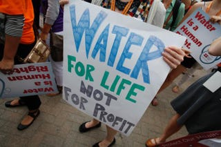 Demonstrators hold signs as they protest against the Detroit Water and Sewerage Department July 18, 2014, in Detroit. The department has disconnected water to thousands of Detroit residents who are delinquent with their bills.Joshua Lott/Getty Images