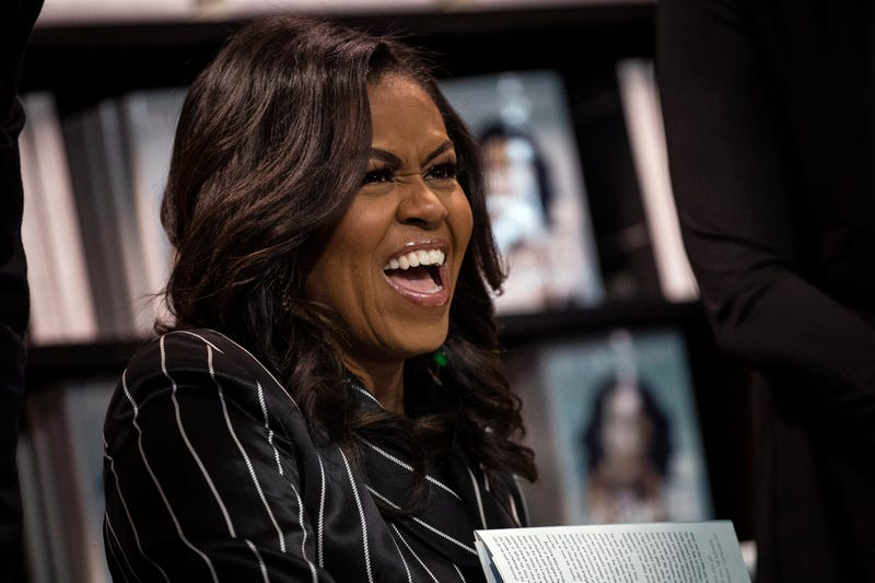 Michelle Obama laughs while signing copies of her new book 'Becoming' during a book signing event at a Barnes & Noble bookstore, November 30, 2018 in New York City.