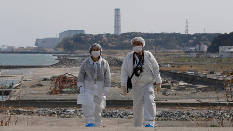 Wearing protective clothing and masks, a husband and wife walk along the coast damaged by the 2011 tsunami, with the Fukushima plant in the background. (Photo: AP)