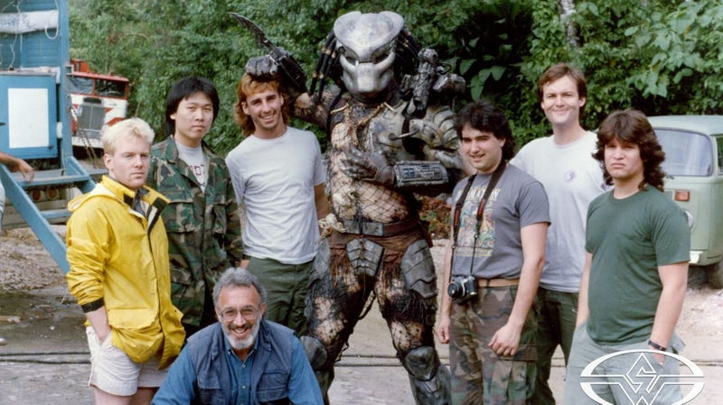 Stan Winston and his crew on the set of Predator. Left to right: Shane Mahan, Steve Wang, Stan Winston (crouching), Brian Simpson, Kevin Peter Hall (as Predator), Shannon Shea, Richard Landon, and Matt Rose.