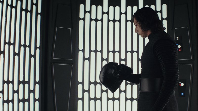 Kylo Ren (Adam Driver) contemplates redecorating the side of a turbolift with bits of his helmet during The Last Jedi.
