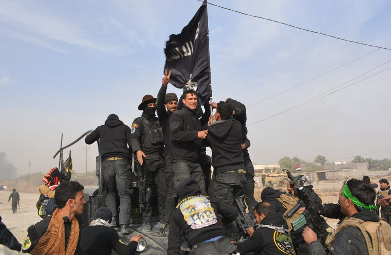 Iraqi-government forces celebrate while holding an Islamic Sate flag northeast of Baghdad on Jan. 26, 2015, near the town of Muqdadiyah. YOUNIS AL-BAYATI/AFP/Getty Images)