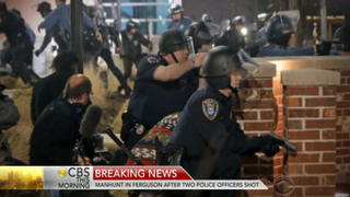 Police officers in Ferguson, Mo., crouch behind brick pillars after shots ring out early morning March 12, 2015, during a protest in front of police headquarters. CBS News Screenshot