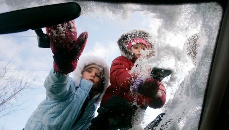 Unos niños le ayudan a su abuela a limpiar el parabrisas.