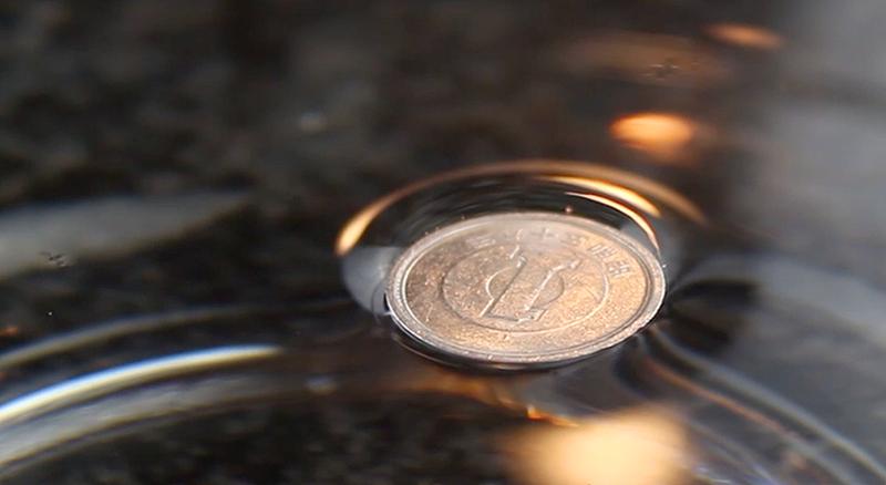 Illustration for article titled Cómo lograr que una moneda de metal flote sobre el agua (y por qué lo hace)