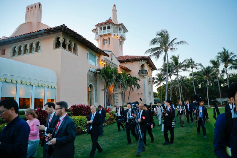 Members of the U.S. and Japanese media walk across the grounds of President Donald Trump's Mar-a-Lago club during a visit by Japanese Prime Minister Shinzo Abe and his wife, Akie Abe, on April 18, 2018, in Palm Beach, Fla.