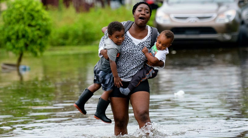 Terrian Jones feels something move in the water as she brings these two boys to their mother during the storm in New Orleans on July 10, 2019.