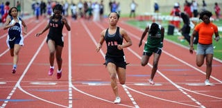 Manaiza Kelley, in a skort, finishes first in the 100-meter dash. (Jonathan Newton/Washington Post)