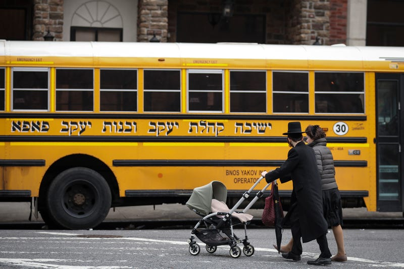A couple pushing strollers walk past the Yeshiva Kehilath Yakov School South Williamsburg.