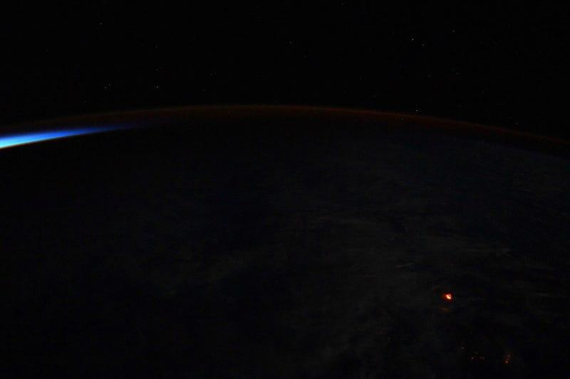 El punto naranja en la foto es el resplandor de la lava desde el espacio.