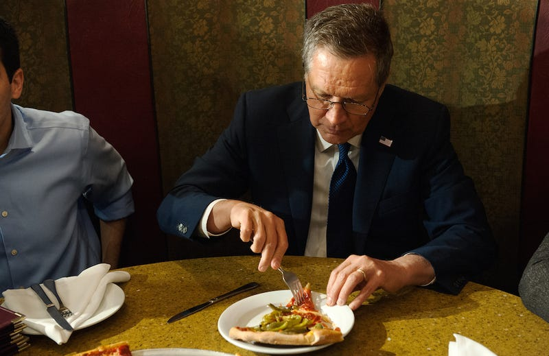 Ohio Gov. John Kasich pokes curiously at a slice of pizza with a fork. (Image via Getty)