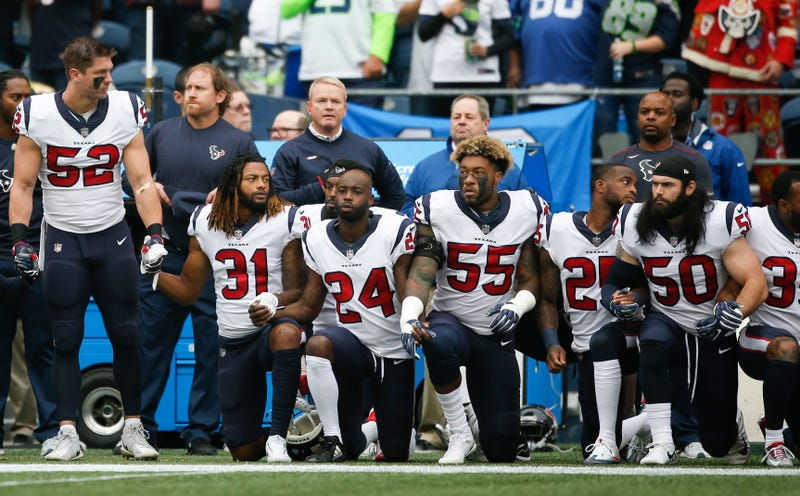 Members of the Houston Texans stand and kneel before the game against the Seattle Seahawks at CenturyLink Field in Seattle on Oct. 29, 2017. (Otto Greule Jr./Getty Images)