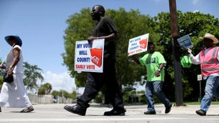 Voters hold up signs as they walk to an early-voting site in Miami on Aug. 11, 2014, to cast their ballots.Joe Raedle/Getty Images