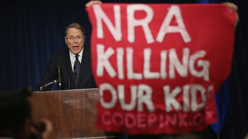 A demonstrator from CodePink holds up a banner as National Rifle Association Executive Vice President Wayne LaPierre delivers remarks during a news conference at the Willard Hotel  in Washington, D.C., on Dec. 21, 2012. (Chip Somodevilla/Getty Images)