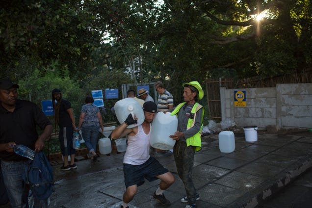 In this Thursday, Feb. 1, 2018 photo, two men help each other carry water at a source for natural spring water in Cape Town, South Africa. The city was predicted to run out of water but rationing has kept that from happening. Photo: AP