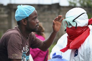 A Liberian burial team puts on protective clothing before retrieving the body of an Ebola victim from his home near Monrovia Aug. 17, 2014. John Moore/Getty Images