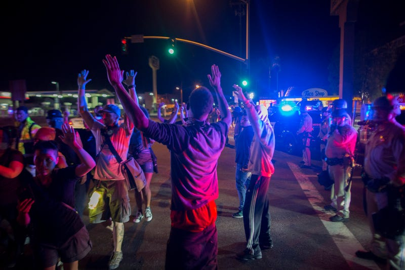 Protesters raise their arms near a line of deputies in riot gear during a march in reaction to the fatal police shooting of an unarmed black man, Alfred Olango, on Sept. 30, 2016, in El Cajon, Calif.David McNew/Getty Images