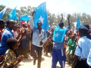 Somali residents raise flags.
