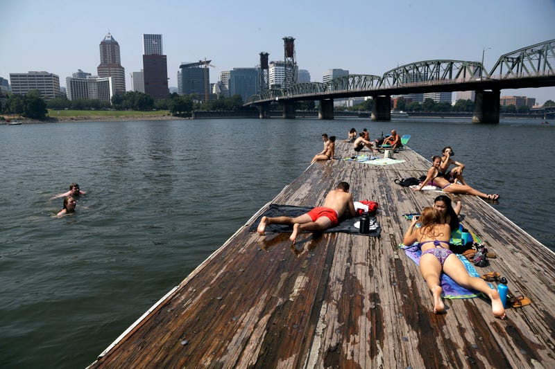 People sunbathe and cool off in the Willamette River with the downtown  skyline visible in the background in Portland, Ore., Wednesday, Aug. 2,  2017. AP Images