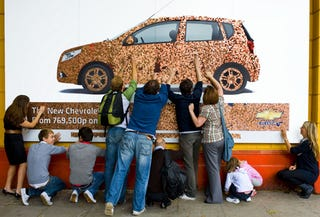 Illustration for article titled Chevy Aveo Billboard Makes Cents, Weighs Untold Pounds