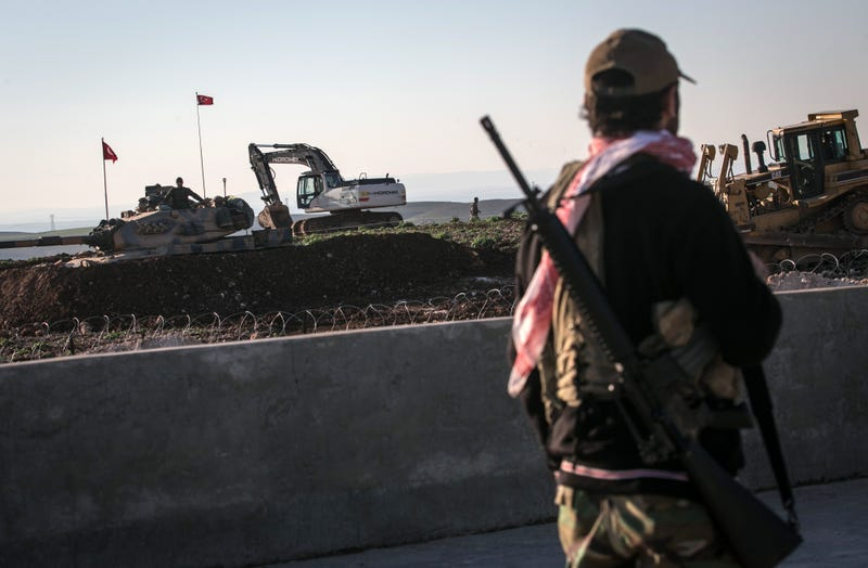 A Syrian Kurdish militia member of YPG patrols near a Turkish army tank as Turks work to build a new Ottoman tomb in the background in Esme village in Aleppo province, Syria, Sunday, Feb. 22, 2015. Turkey launched an overnight military operation into neighboring Syria to evacuate troops guarding an Ottoman tomb and to move the crypt to a new location, Turkish Prime Minister Ahmet Davutoglu said Sunday. Davutoglu said they plan to build a new Ottoman tomb in Esme village, close to Turkey-Syria border. (AP Photo/Mursel Coban, Depo Photos)