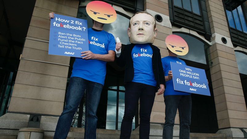 A protester wearing a mask of Facebook founder Mark Zuckerberg, in between men wearing angry face emoji masks. London, 2018.