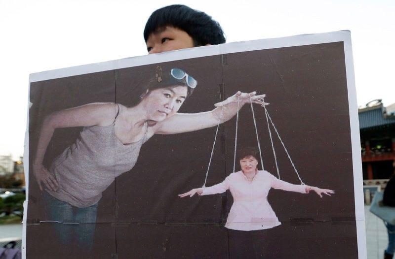 Un manifestante sostiene una pancarta con una imagen de Choi Soon-Sil manipulando a la presidenta de Corea del Sur como si fuera un títere. Foto: AP Images.