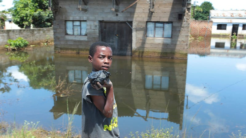 A young boy walks past a flooded home in Inchope, Mozambique, March 25, 2019.