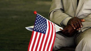 In this 22 May 2006 file photo, Jeneba Kanu, originally from Sierra Leone, holds a US flag while waiting to become a US citizen, during a naturalization ceremony at George Washington's Mount Vernon in Alexandria, Virginia.  JIM WATSON/AFP/Getty Images