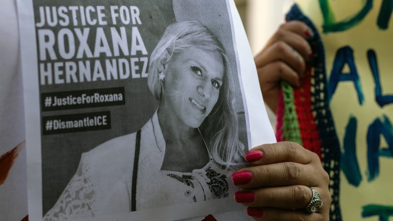 Woman holds #JusticeforRoxsana flyer at a march in her honor
