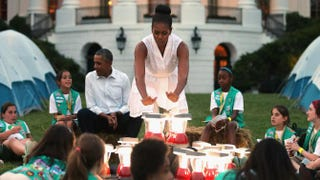"""First lady Michelle Obama pretends to warm herself over a """"fire"""" made from battery-powered lanterns as she and President Barack Obama host a group of Girl Scouts from across the country for a campout on the South Lawn of the White House June 30, 2015, in Washington, D.C.Chip Somodevilla/Getty Images"""