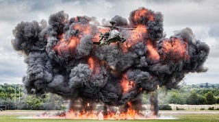 Illustration for article titled Here's an Apache attack helicopter flying away from a monster explosion