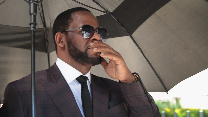 R&B singer R. Kelly covers his mouth as he speaks to members of his entourage as he leaves the Leighton Criminal Courts Building following a hearing on June 26, 2019, in Chicago.
