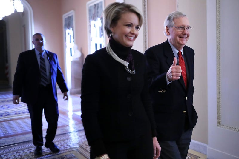 Senate Majority Leader Mitch McConnell (right) gives a thumbs-up as he and his director of operations, Stephanie Muchow, head for the Senate floor at the U.S. Capitol in Washington, D.C., on Dec. 1, 2017. (Chip Somodevilla/Getty Images)