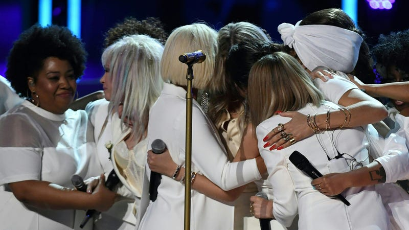 Performers gather around Kesha after her Grammys performance. (Photo: Timothly Clary/Getty Images)