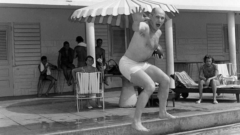 "The original Associated Press caption for this photo: ""Y.A. Tittle, quarterback for the New York Football Giants who is best known for his passing, carries the ball as he jumps into pool during the ball as he jumps into pool during vacation at San Juan, Puerto Rico on May 8, 1964. Tittle is one of a contingent of Giants visiting Puerto Rico to teach football to the natives."""