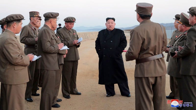 North Korean dictator Kim Jong Un (center) talks with military advisors in a photo released by the NK government