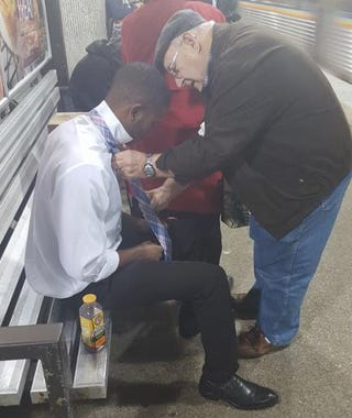 The elderly man shows the young man how to tie his tie. Redd Desmond Thomas