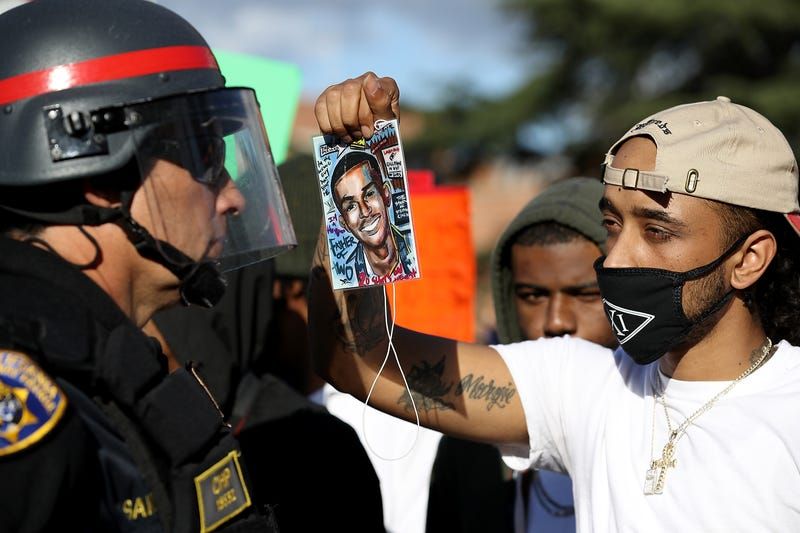 A Black Lives Matter protester holds a photo of Stephon Clark in front of a California Highway Patrol officer as they block an entrance to Interstate 5 during a demonstration March 23, 2018, in Sacramento, Calif.