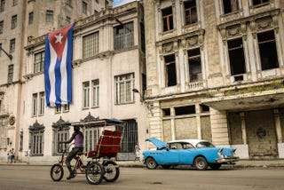A bike-taxi and a vintage American car are seen in front of a building decorated with a large Cuban flag on Dec. 31, 2013, in Havana. ADALBERTO ROQUE/AFP/Getty Images