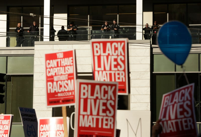 Police officers watch from a shopping mall balcony as a Black Lives Matter protest occurs below on Black Friday in Seattle on Nov. 27, 2015.JASON REDMOND/AFP/Getty Images