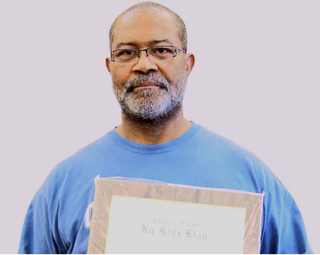 Ron Stallworth holding KKK membership plaque Ron Stallworth/Blackklansman.com