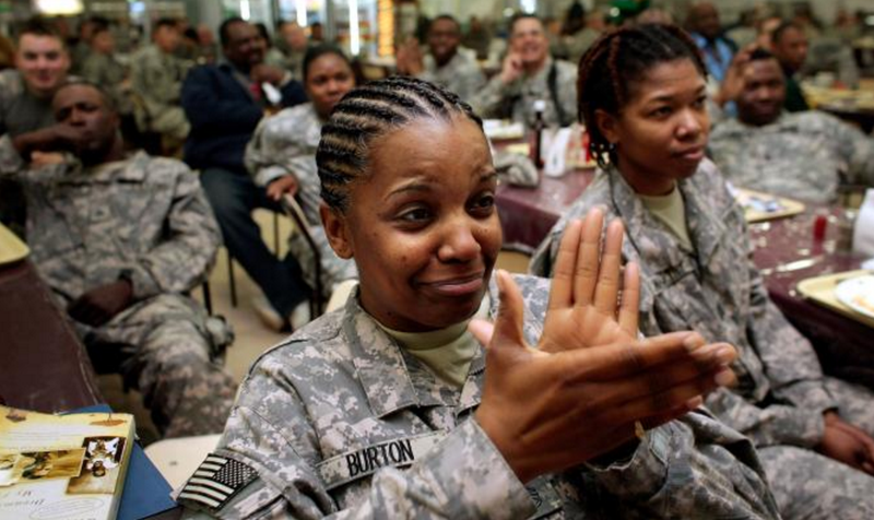 U.S. Army Staff Sgt. Beverlee Burton of Cleveland (left, foreground) cries as she and Capt. Adhana McCarthy watch Barack Obama be sworn in as the 44th president of the United States on Jan. 20, 2009, in the dining hall of Forward Operating Base Kalsu, south of Baghdad. CHRIS HONDROS/GETTY IMAGES