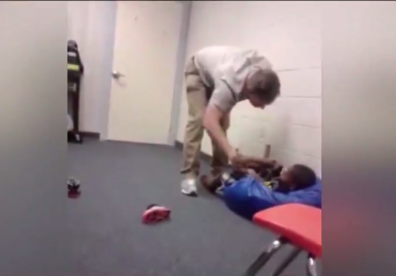 A Snook, Texas, school employee, identified by authorities as Troy Vann, seen in video footage standing over a small child. School officials say they've fired Vann for pushing the child, a prekindergartner, and being verbally inappropriate with him. KVUE screenshot